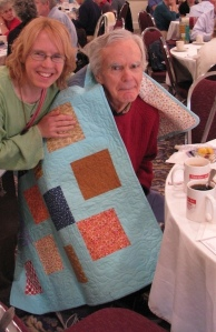 A daughter wraps her father in a quilt by Bob Johnson